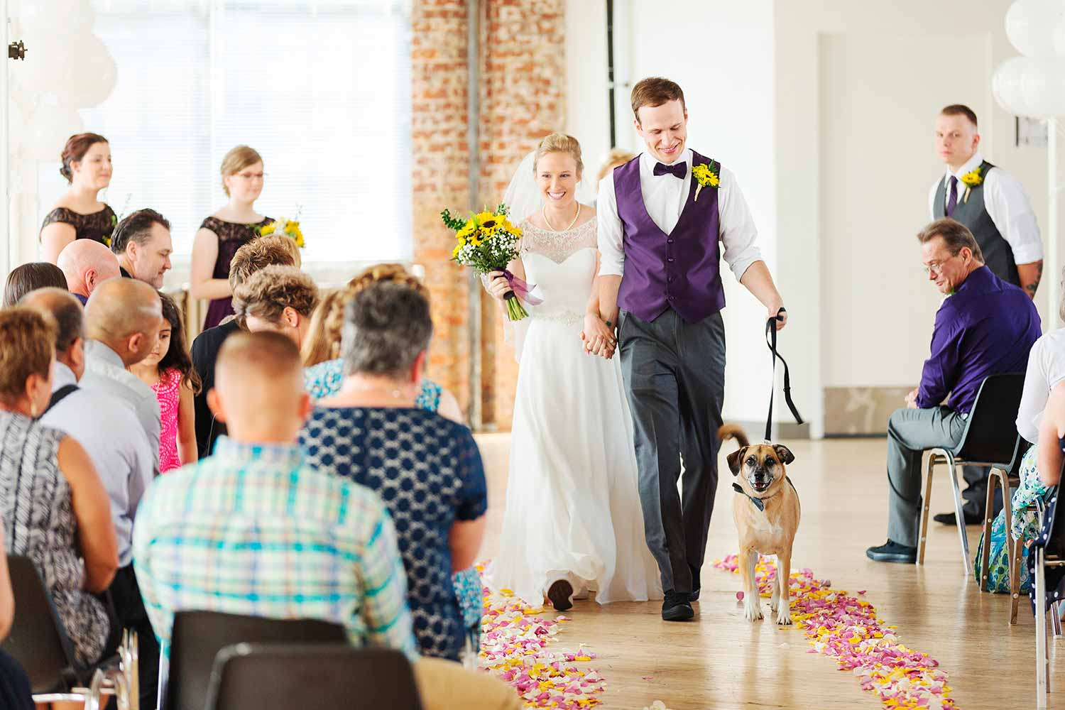 Dog walking with couple at wedding